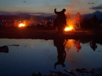 A teenager plays with the camera in the reflections of a stagnant water pond next to their encampment