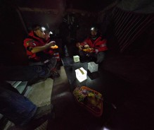 Volunteers share a meal at Korakas lighthouse by the light of headlamps